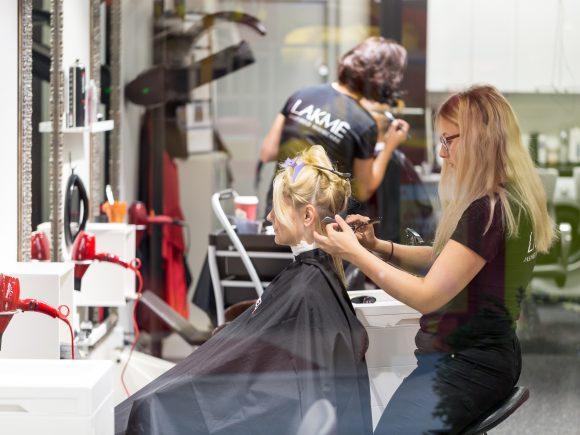 Kampaamopalvelut - Naisen hiuksia leikataan parturituolissa.