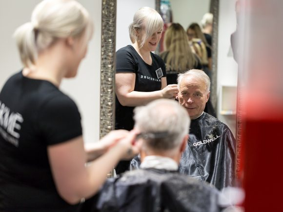 Parturipalvelut - Miehen hiuksia leikataan parturituolissa.